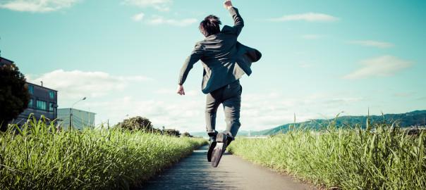道路でジャンプをするスーツのビジネスマン